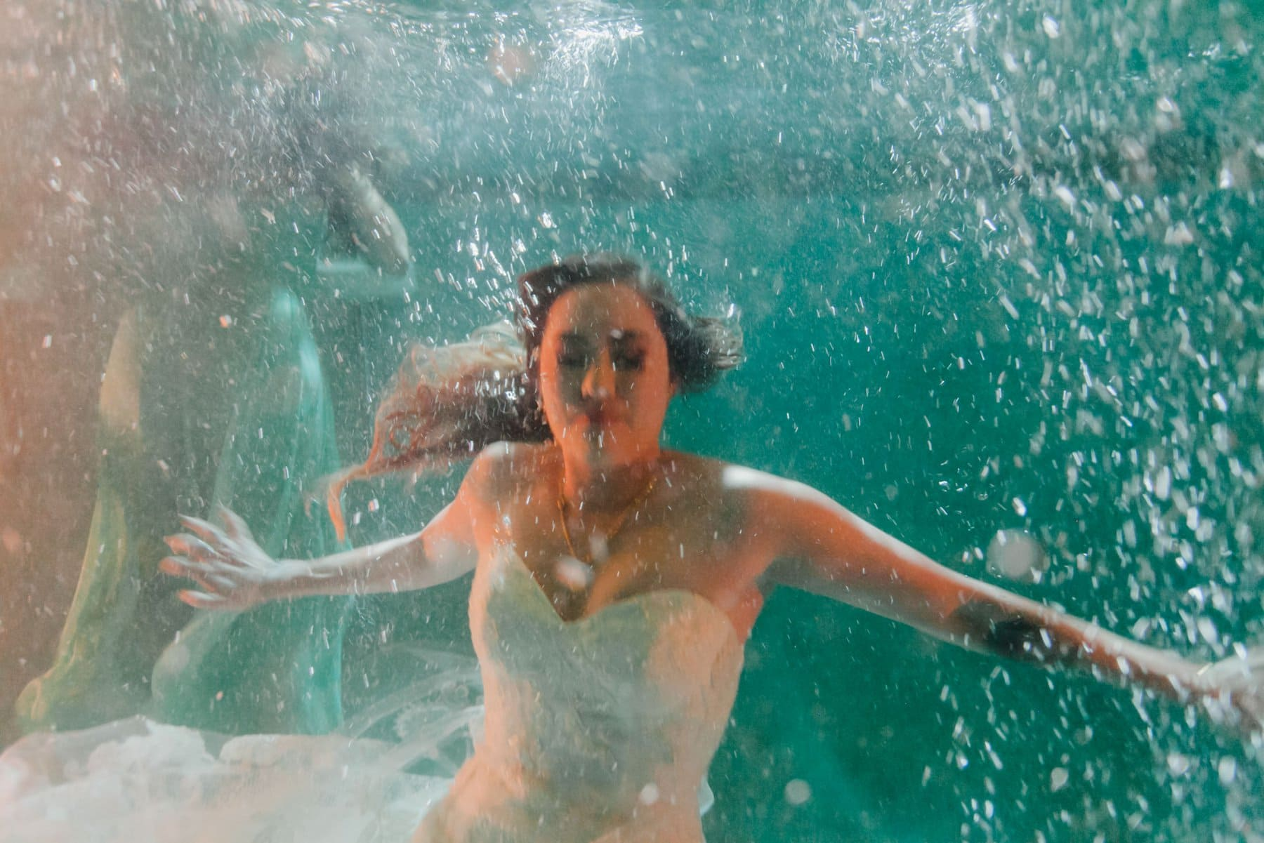 bride jumping into pool at wedding reception underwater