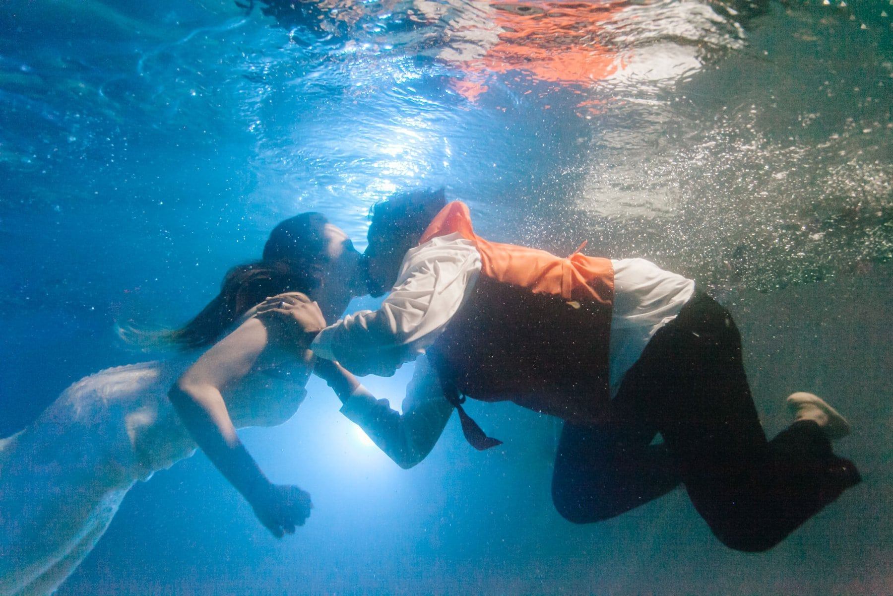 bride and groom jumping into pool at wedding reception underwater