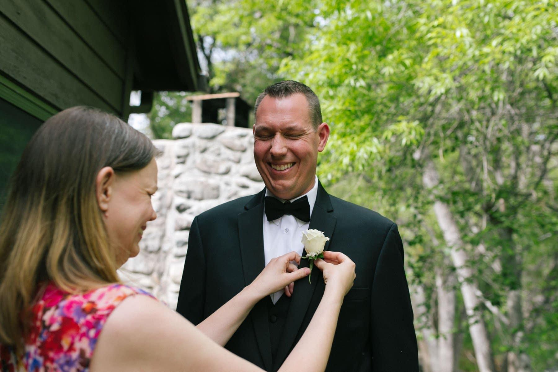 groom getting boutineer pinned Briar Patch Inn wedding