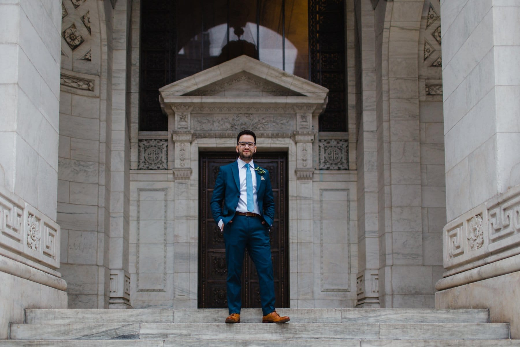 groom standing in front of New York Public Library in Manhattan
