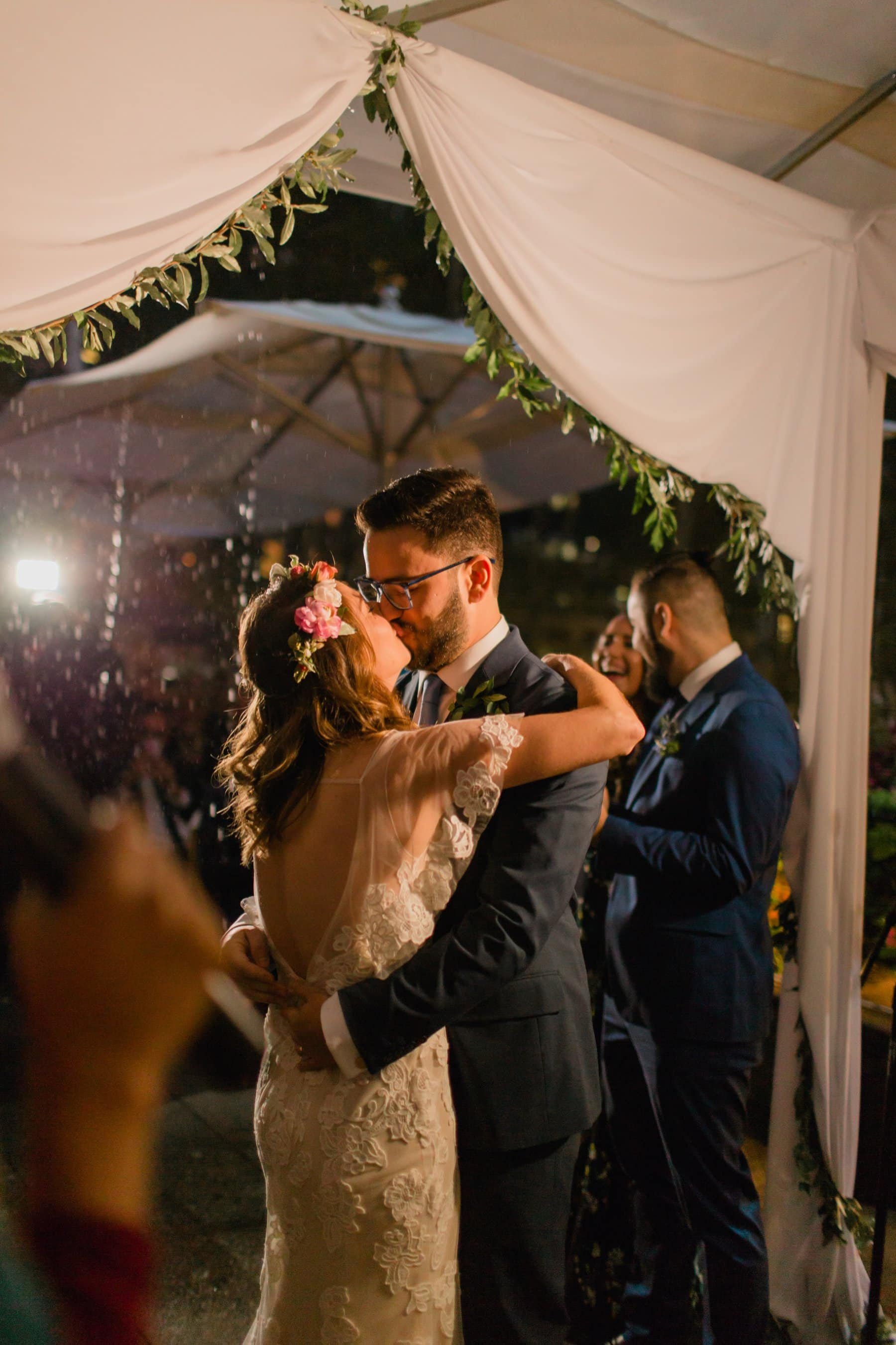 First kiss bride & groom Bryant Park Grill rooftop wedding ceremony in the rain at night