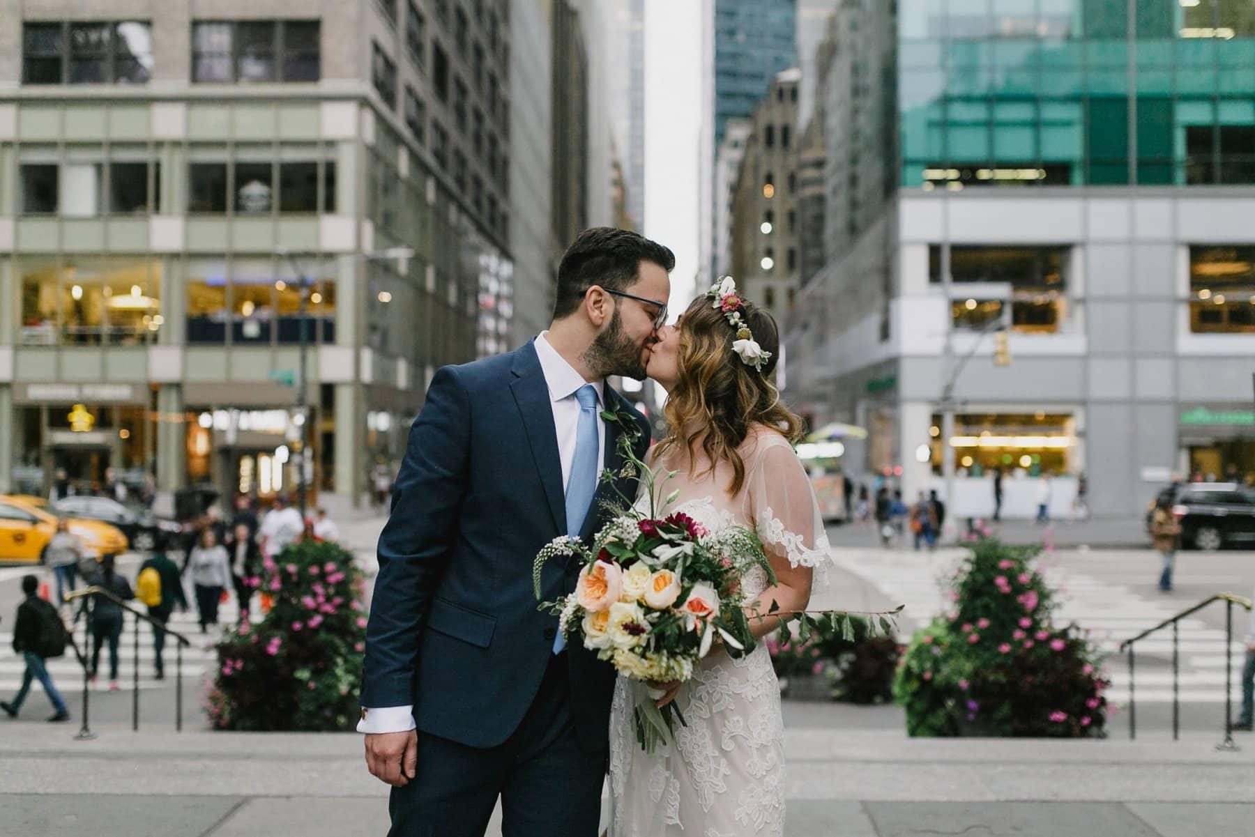 Manhattan wedding bride & groom kissing in front of buildings