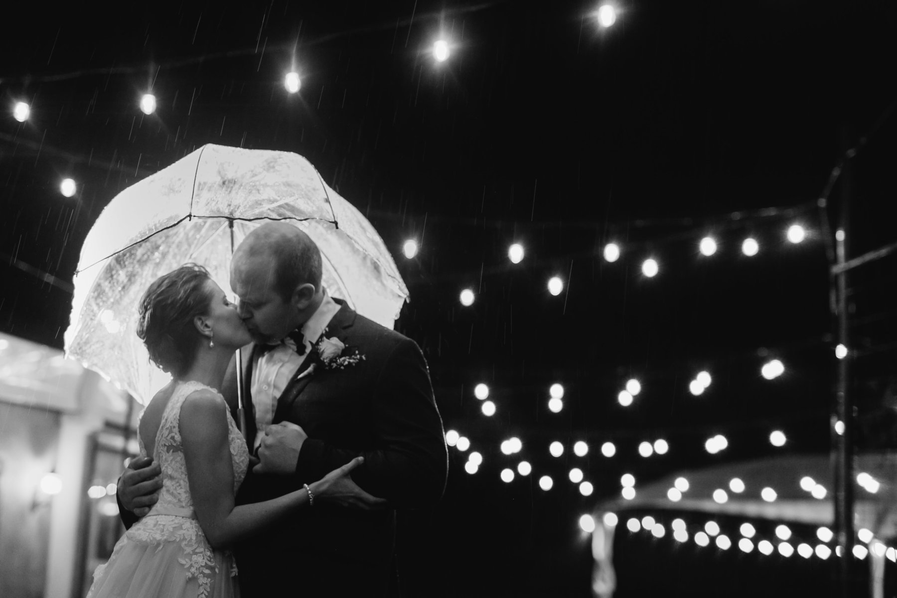 bride & groom under umbrella rainy reception black & white at Gold Canyon Golf Resort