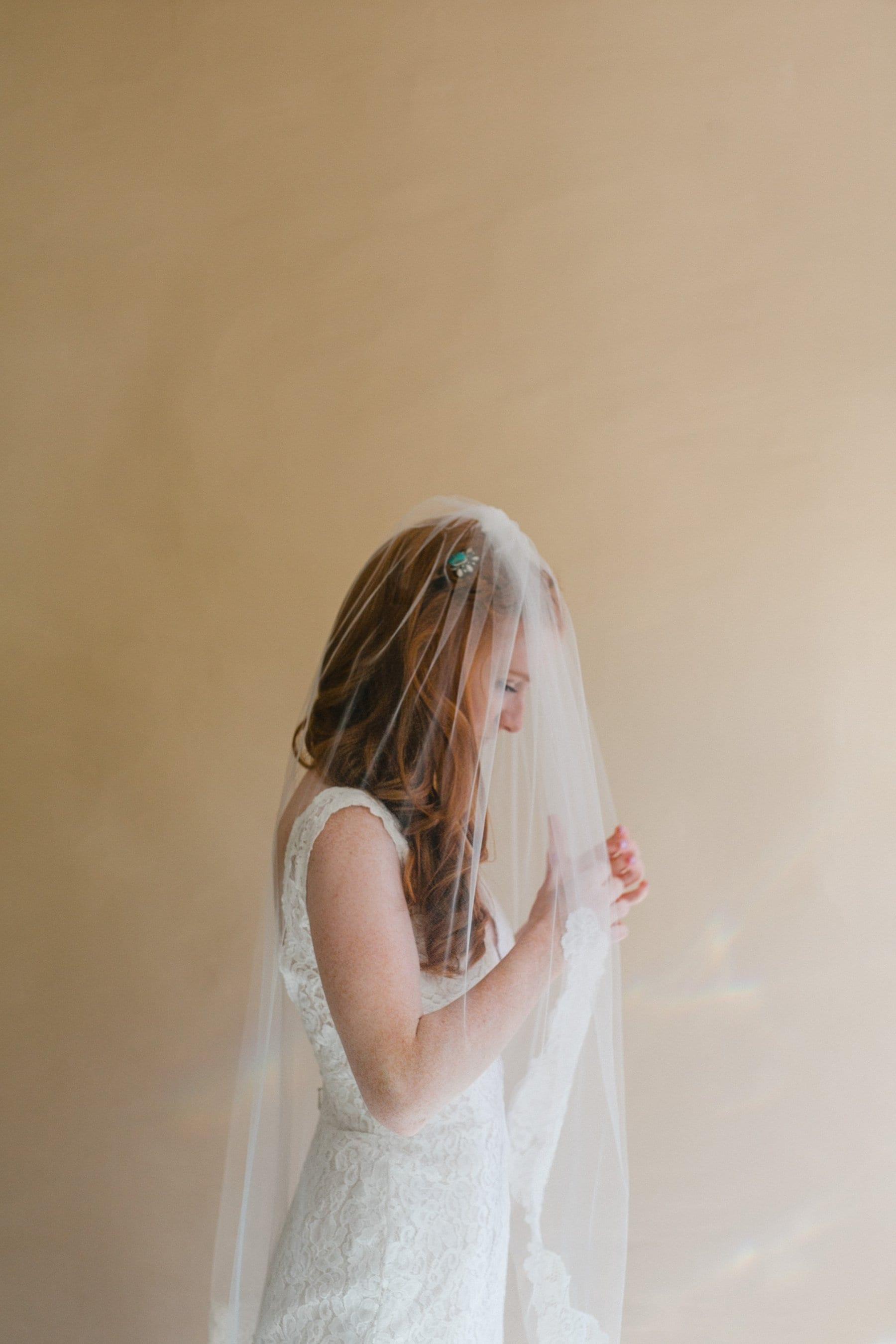 redhead bride in veil getting ready for wedding Phoenix wedding photographer