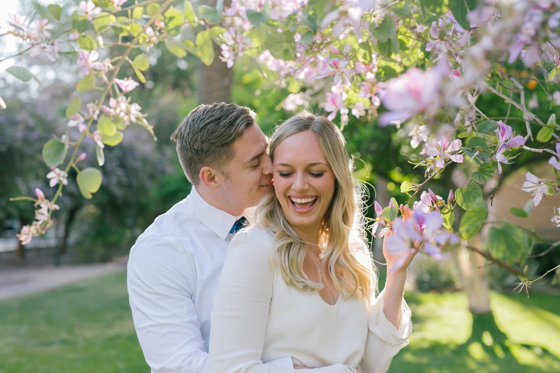 couple genuinely laughing with purple flowers around at Arizona State University engagement photos