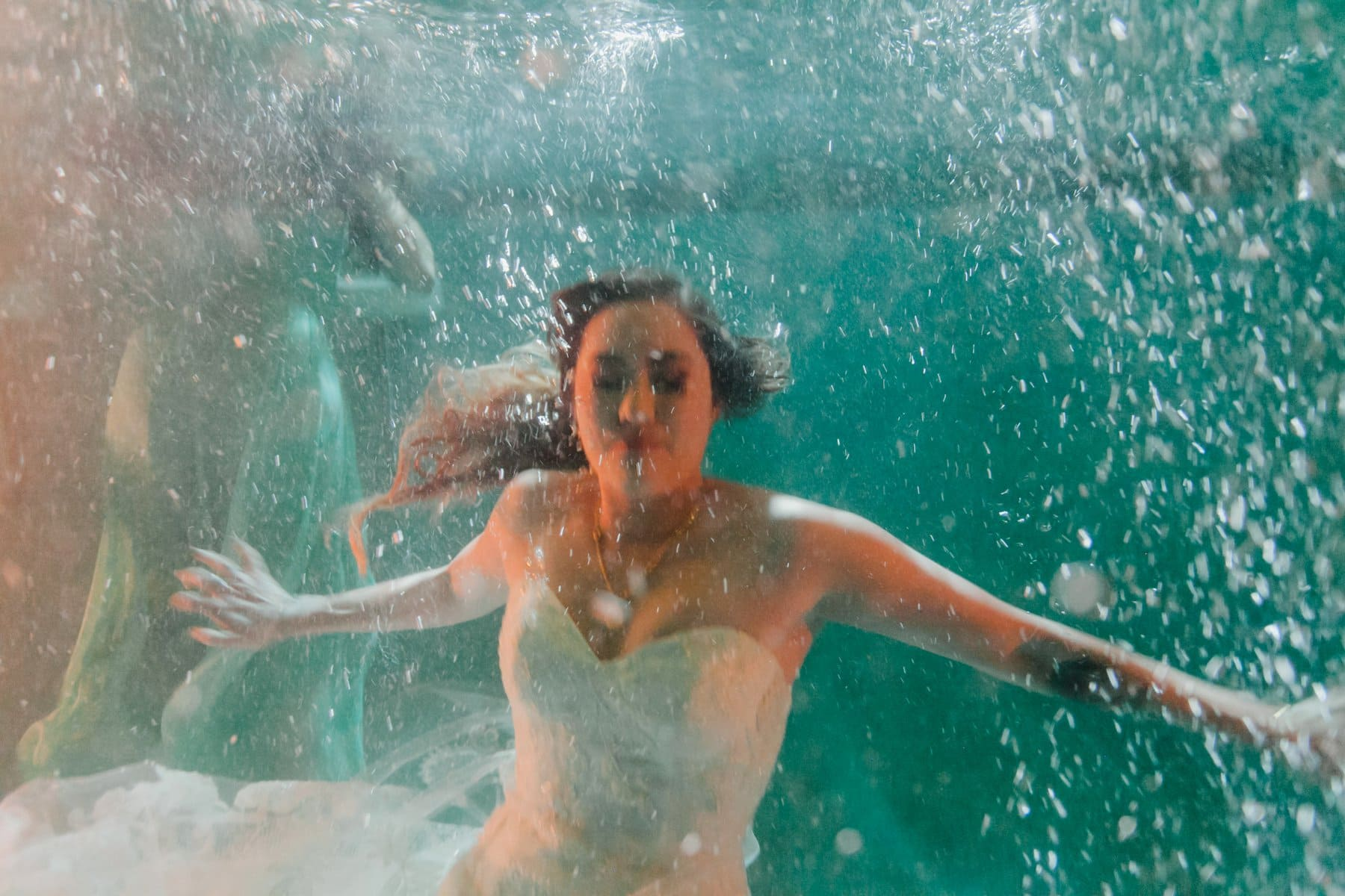 bride jumps into pool at wedding underwater photo