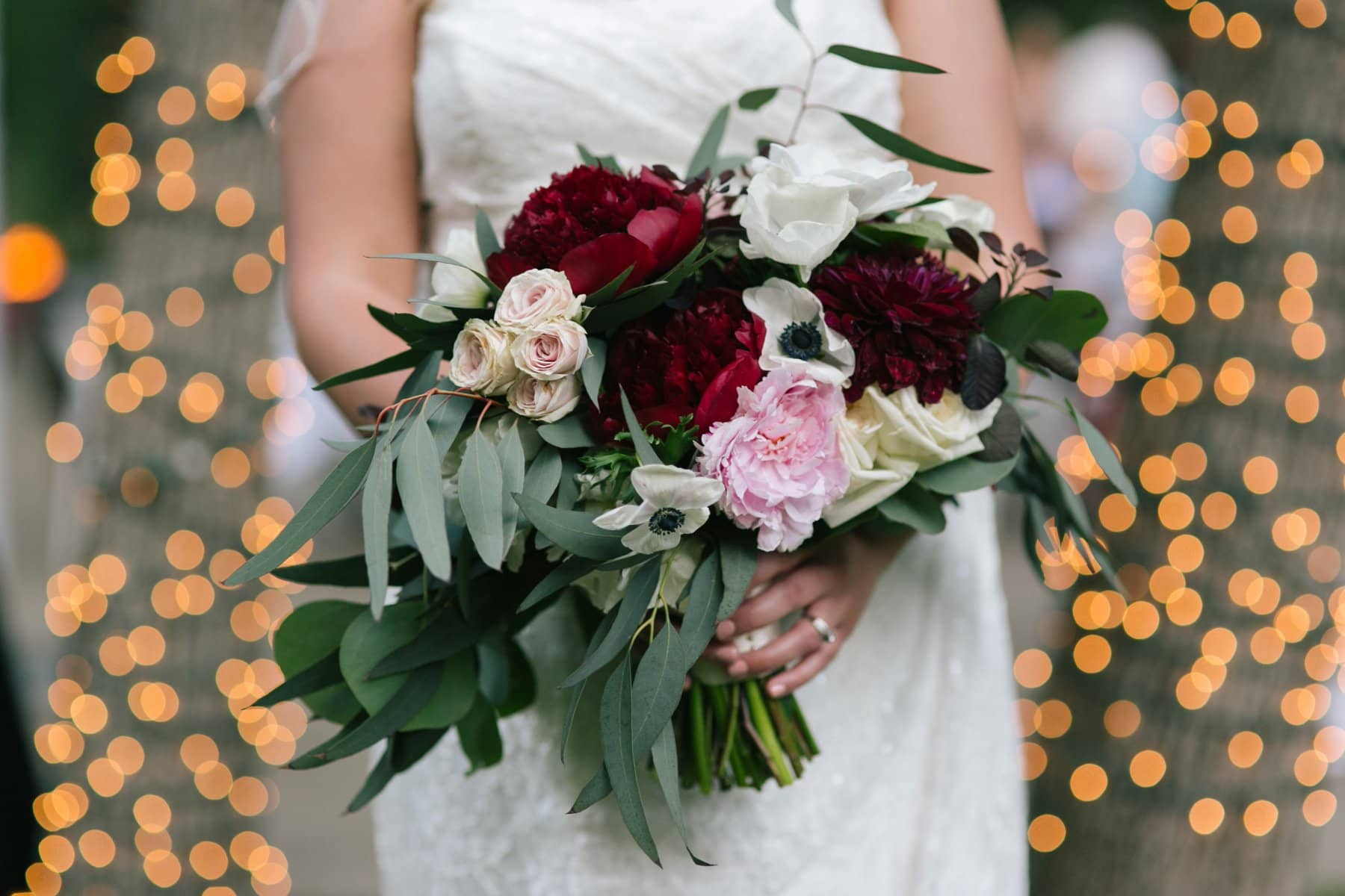 bride holding wedding bouquet with pink & red with lights behind at Junipine Resort wedding photos