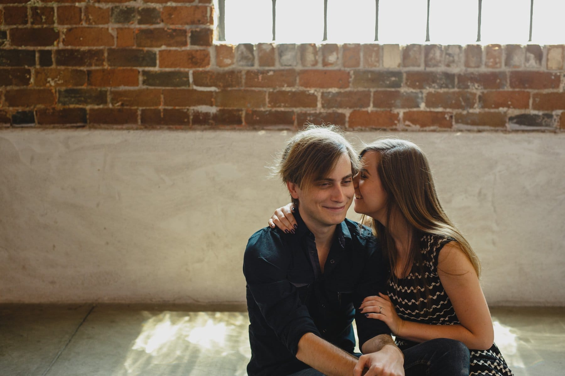 cute couple whispering in ear in downtown warehouse engagement photos