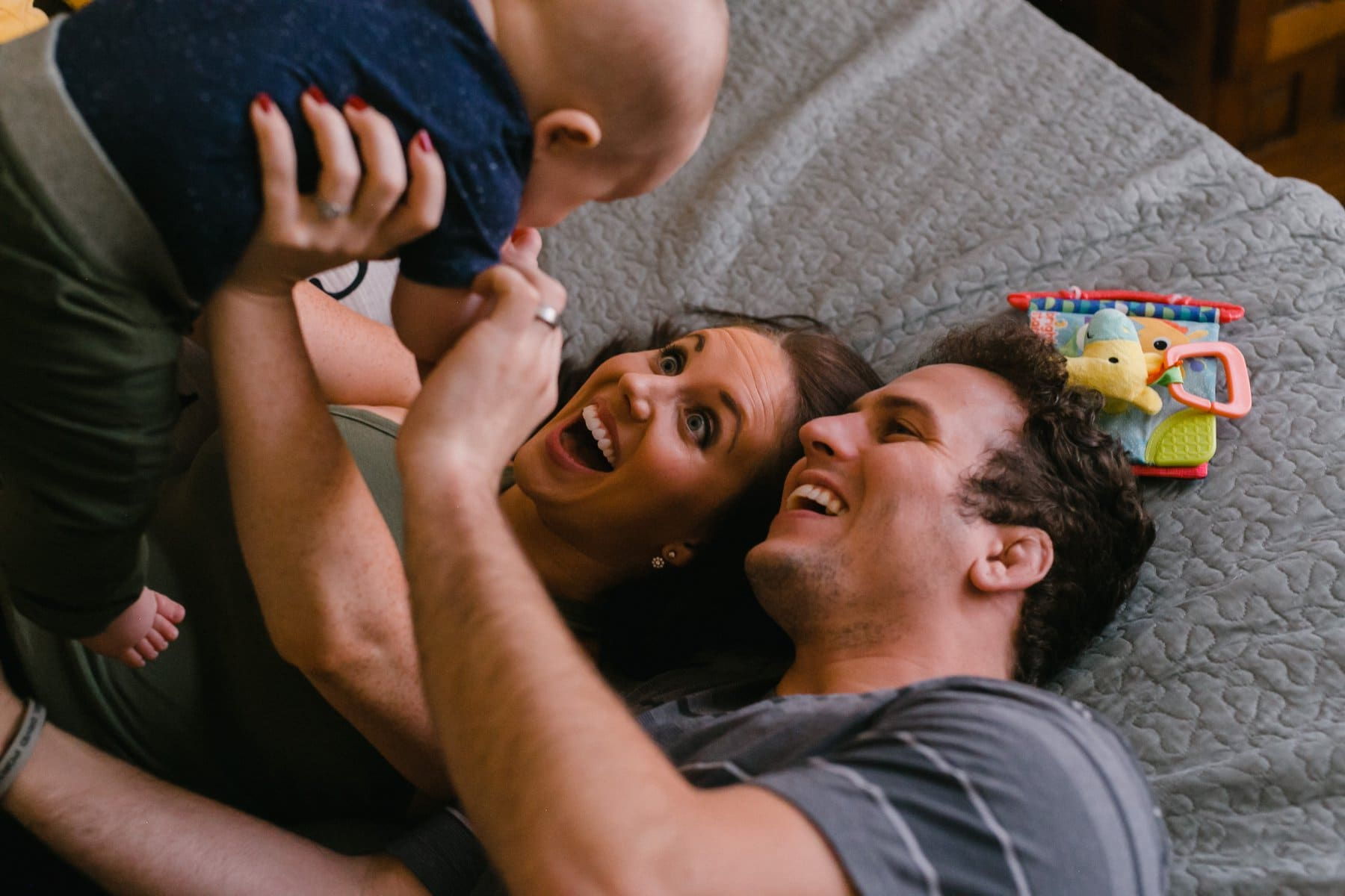 in home session parents looking up at baby on bed Phoenix candid family photographer