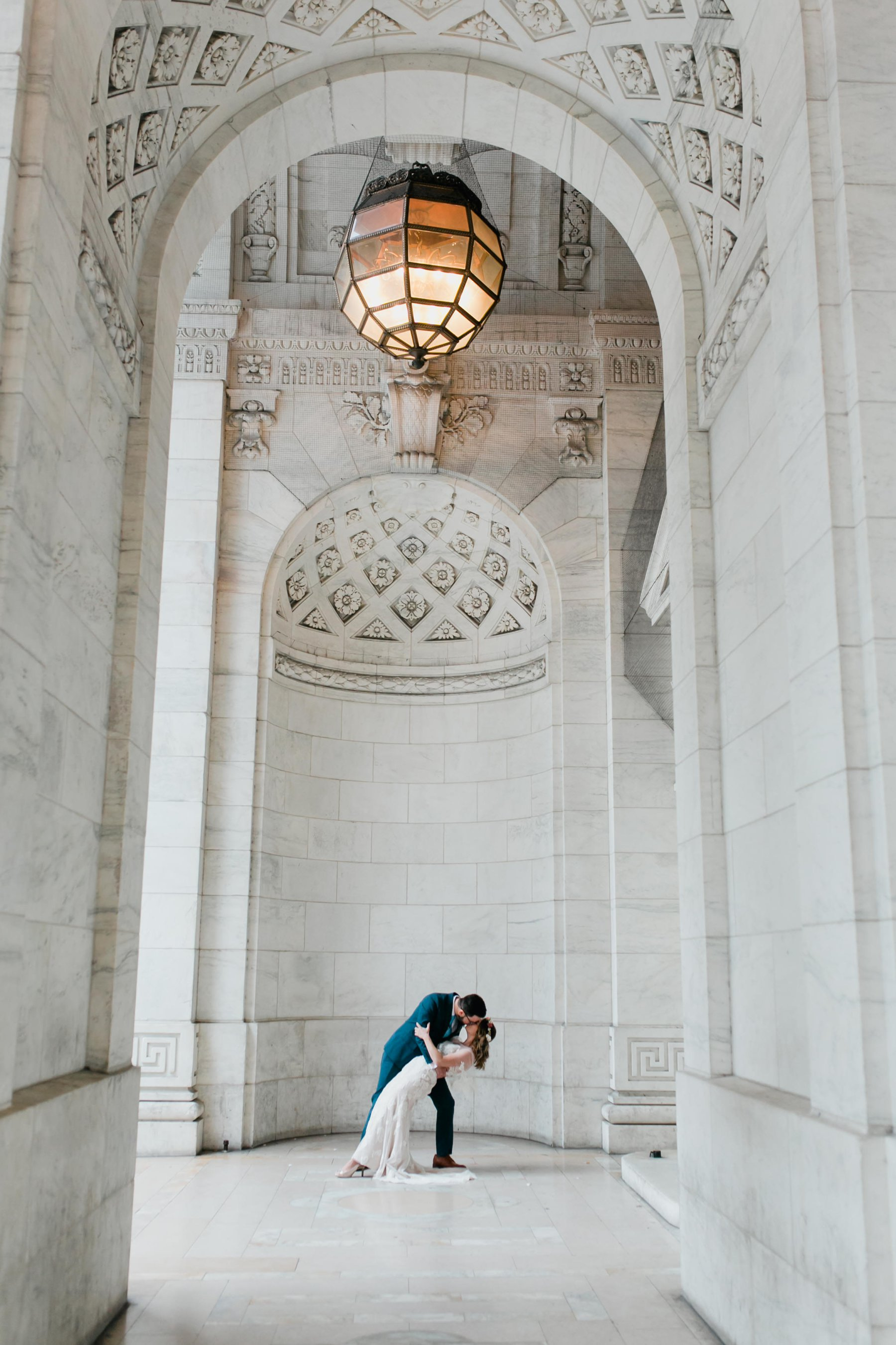 bride & groom dipping in marble halls of New York Public Library Bryant Park