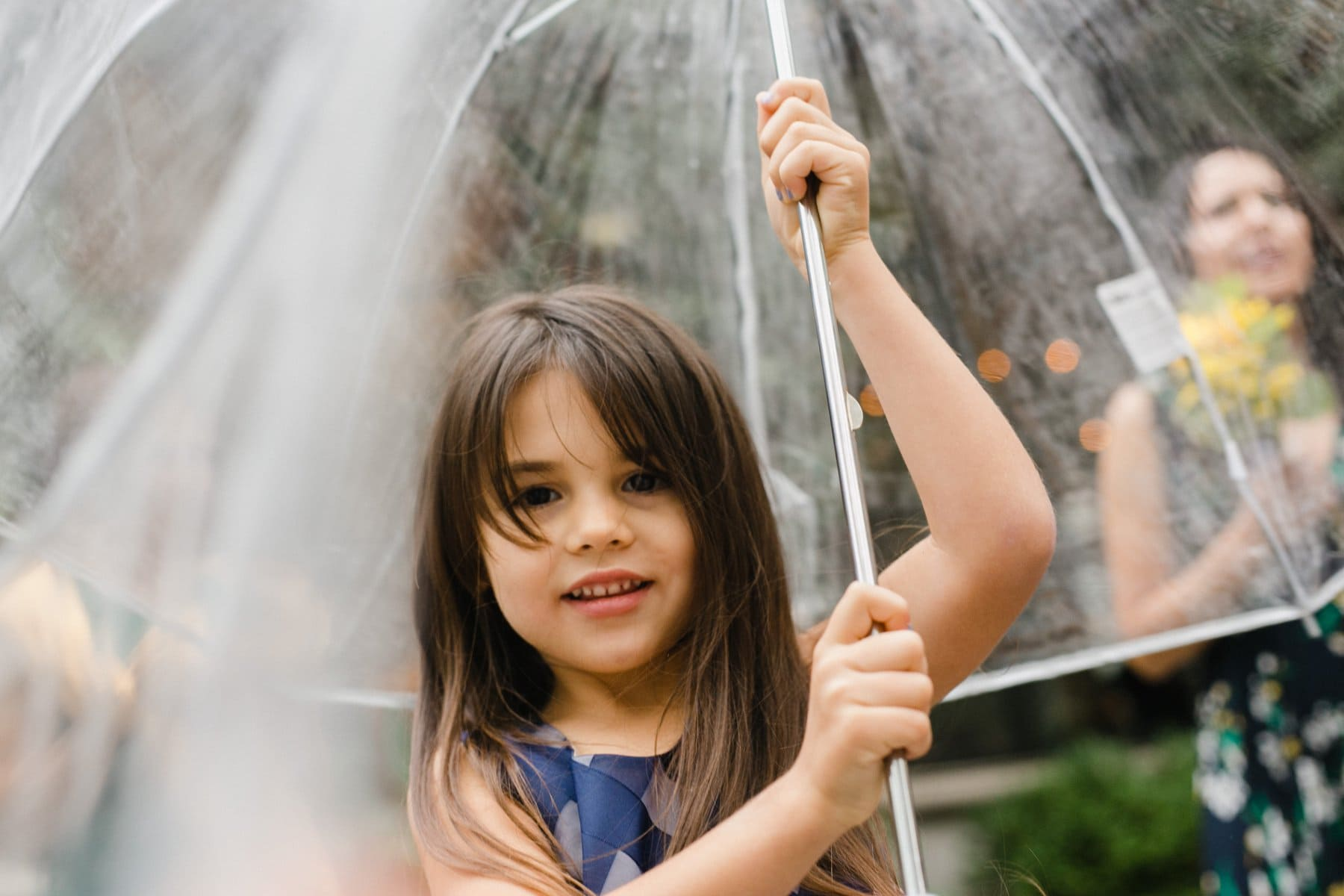 cute little girl playing with clear umbrella