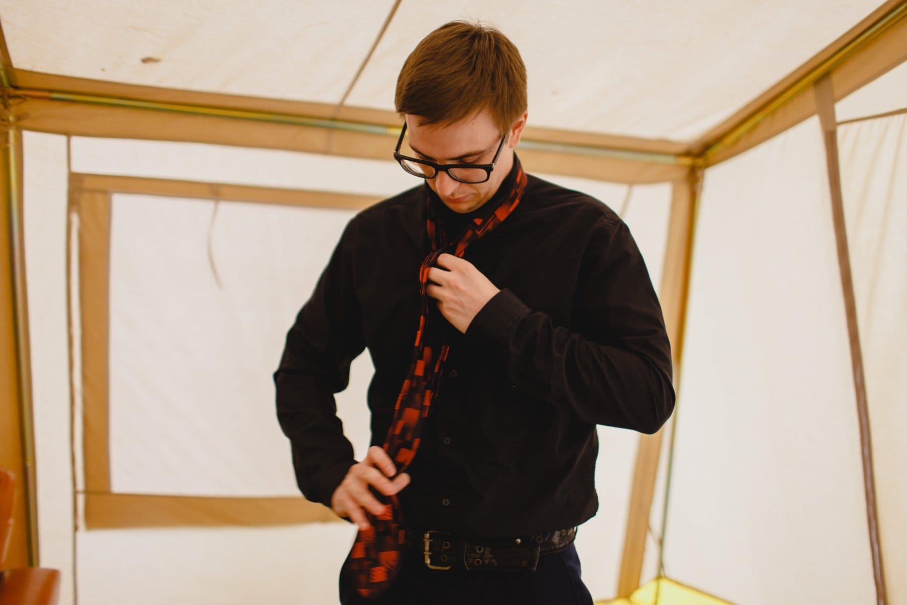 groomsman getting ready in glamping tent Schnepf Farms Meadow wedding