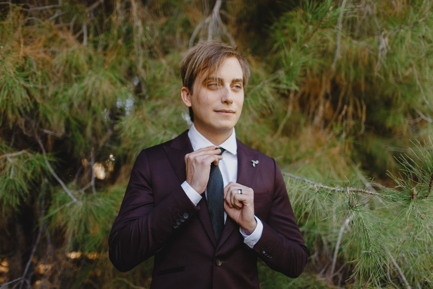groom at the Meadow at Schnepf Farms in custom Magro maroon slim fit suit