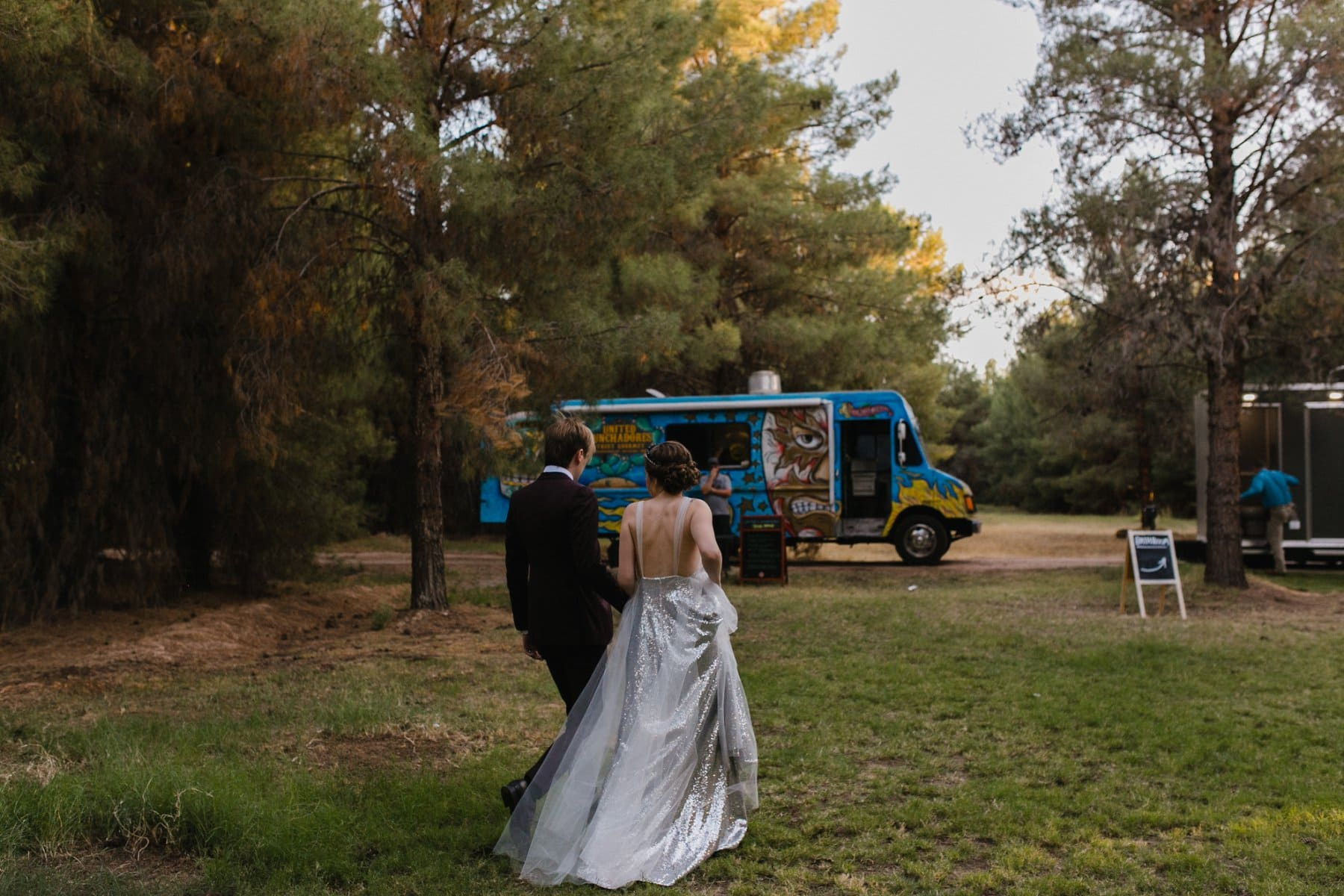 bride & groom walking towards food truck at the Meadow Schnepf Farms reception