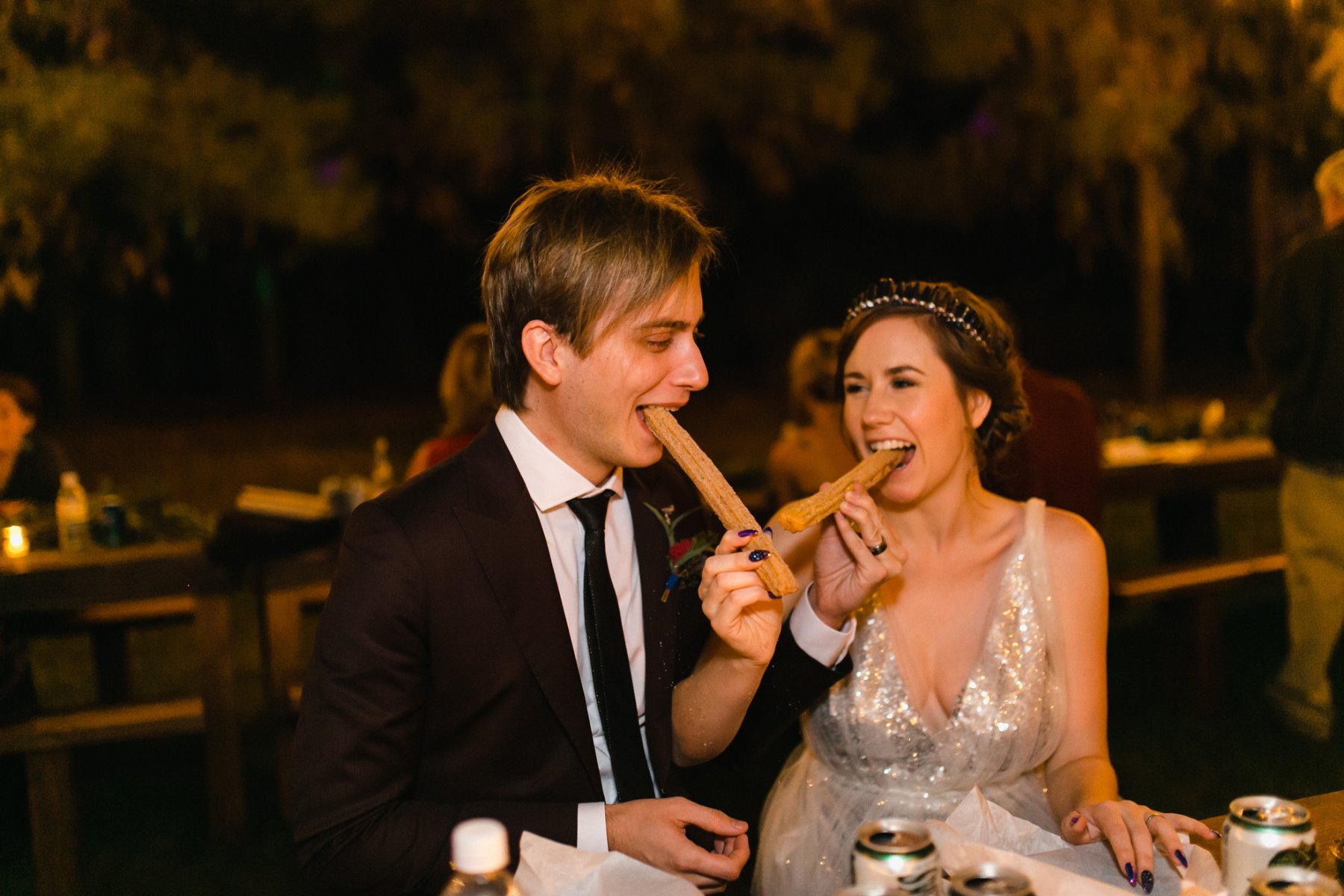 bride & groom eating churros wedding photos the Meadow Schnepf Farms