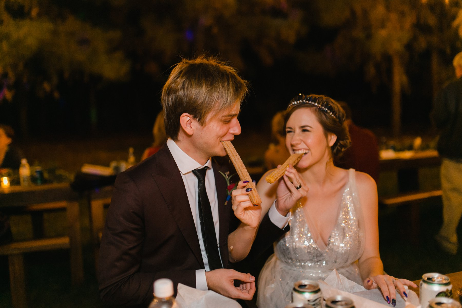 bride & groom eating churros wedding photos the Meadow Schnepf Farms