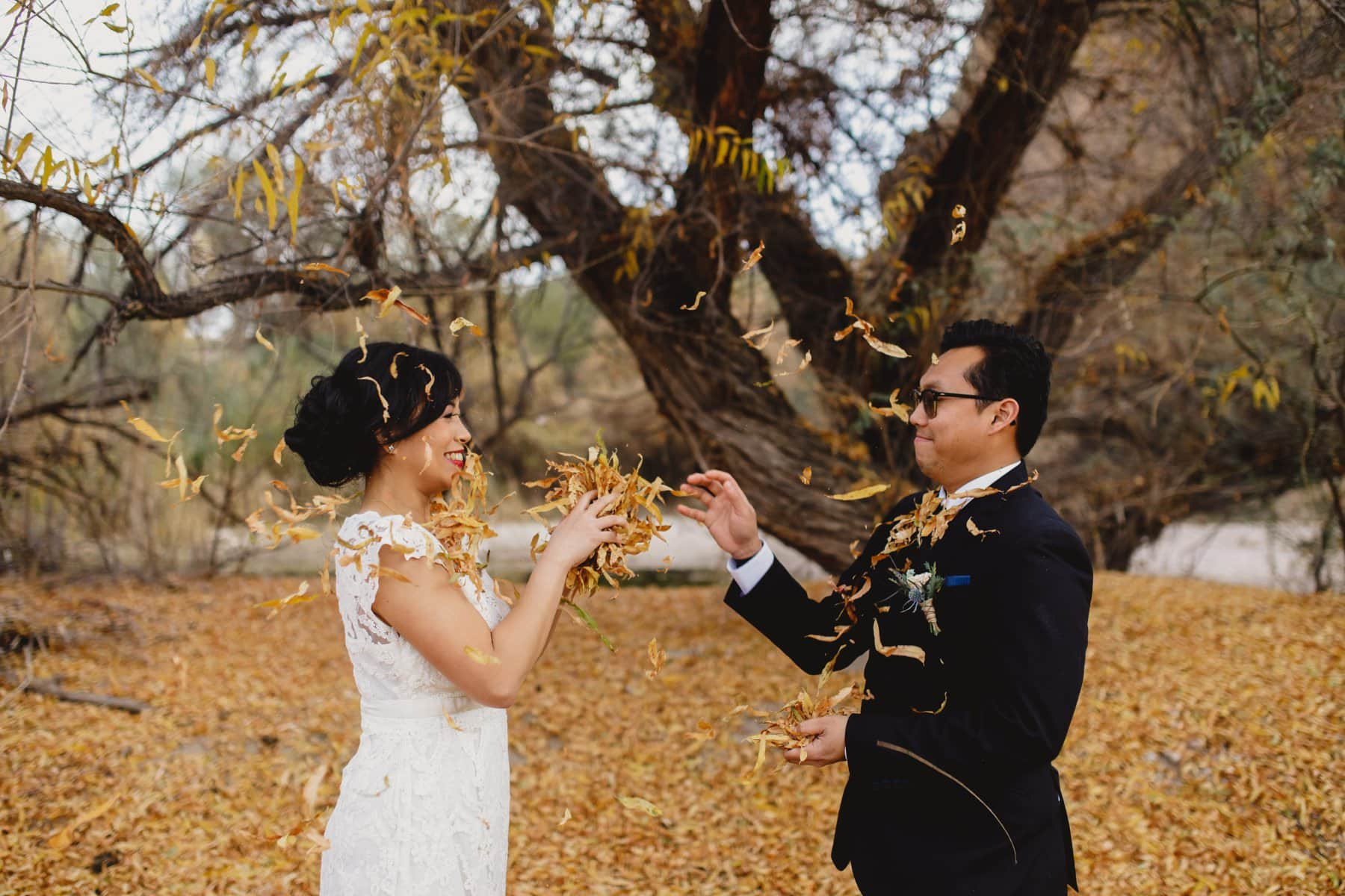 bride and groom tossing leaves at each other Arizona outdoor wedding location