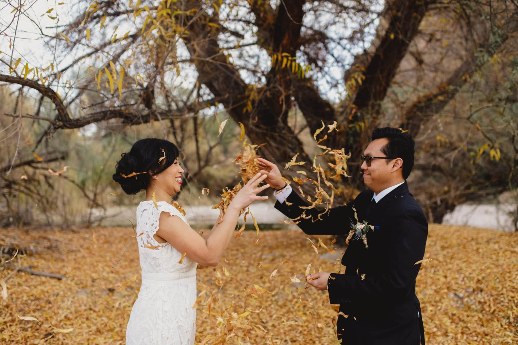 bride & groom throwing leaves at each other fall outdoor Arizona wedding