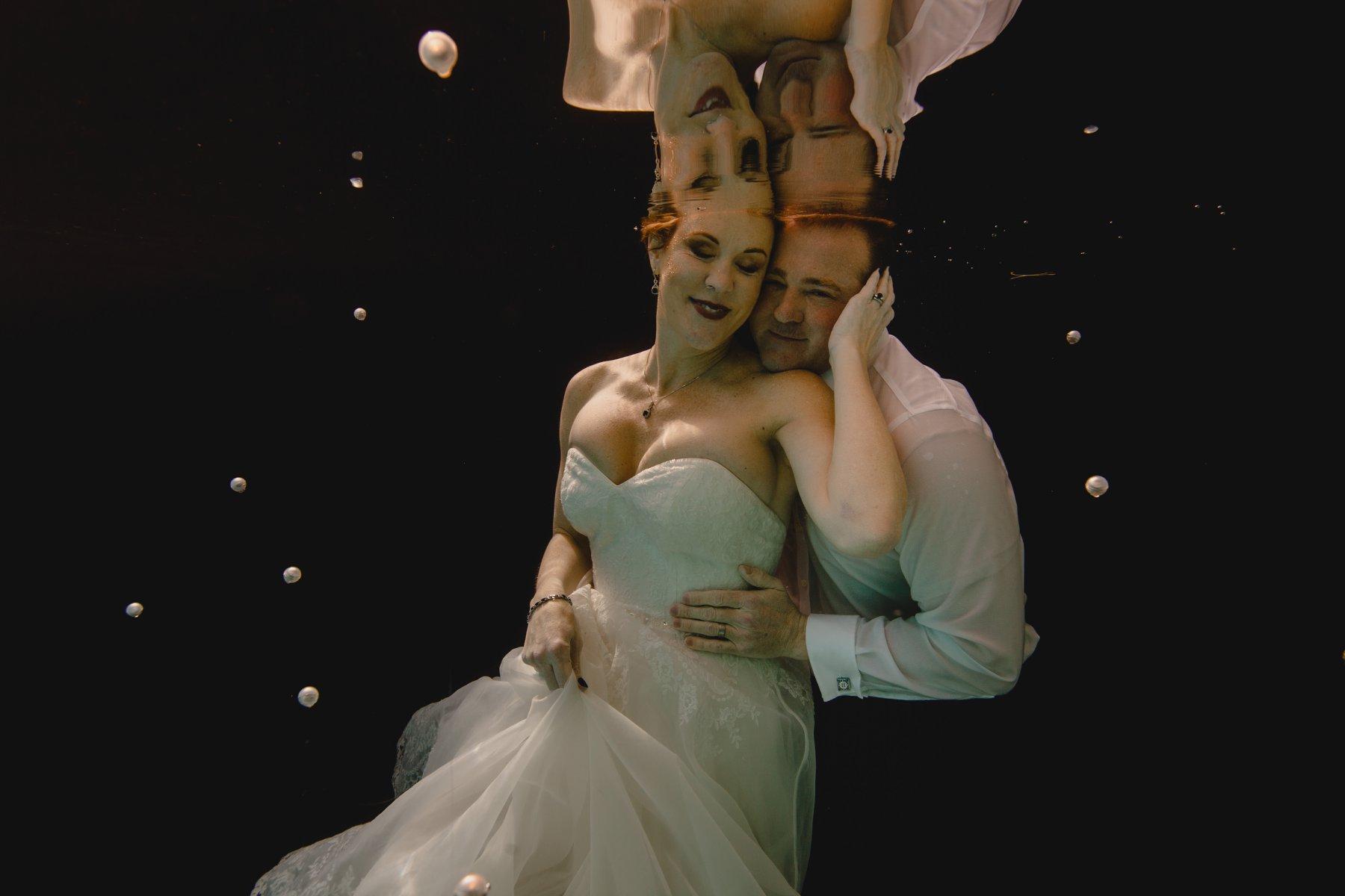 underwater wedding trash the dress photos on black backdrop in a pool Phoenix