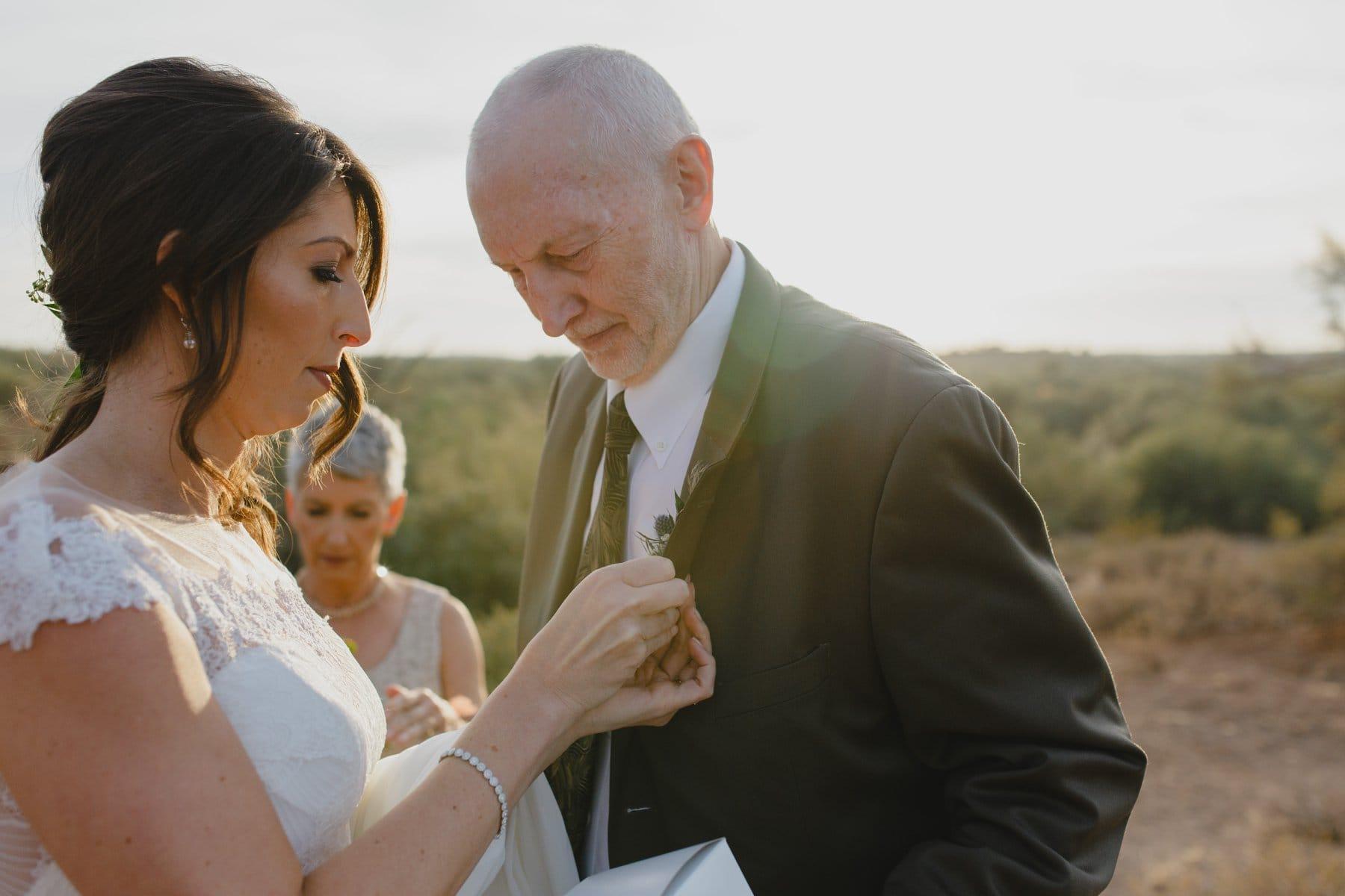 documentary elopement coverage Arizona desert bride pinning boutonniere on dad