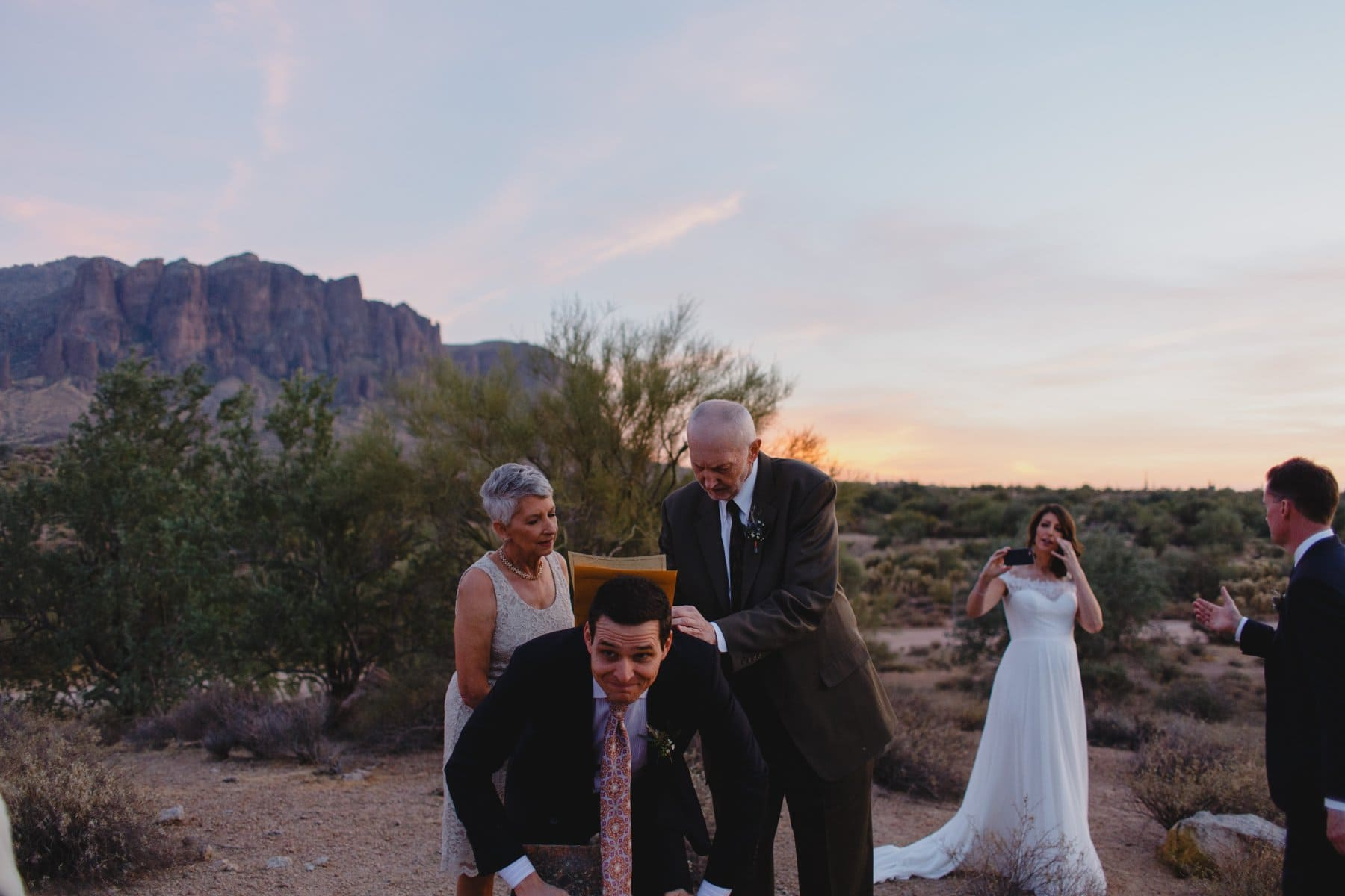 documentary candid elopement photographer in Arizona signing marriage license on officiant's back