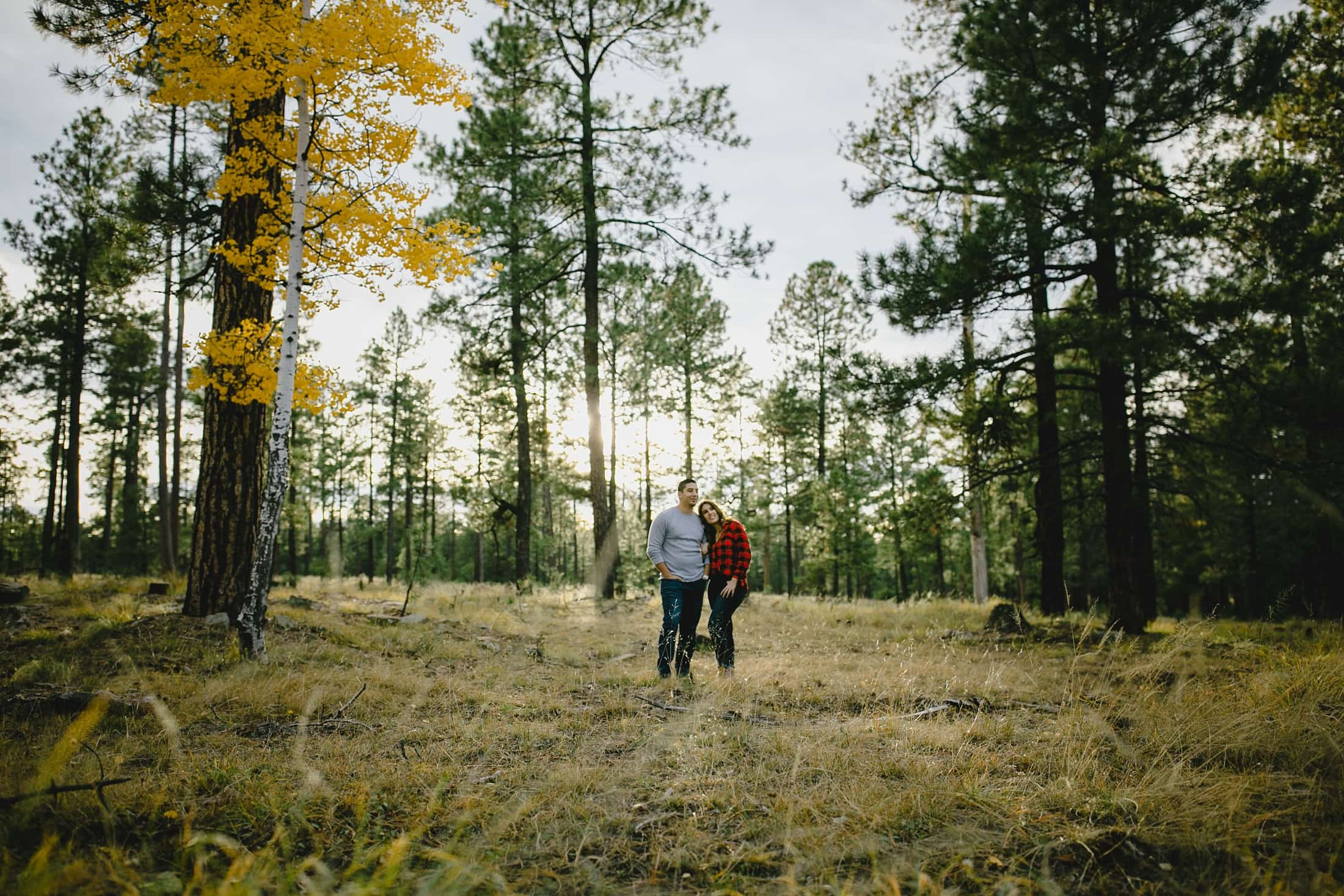 couple standing in pine tree forest in fall in Arizona