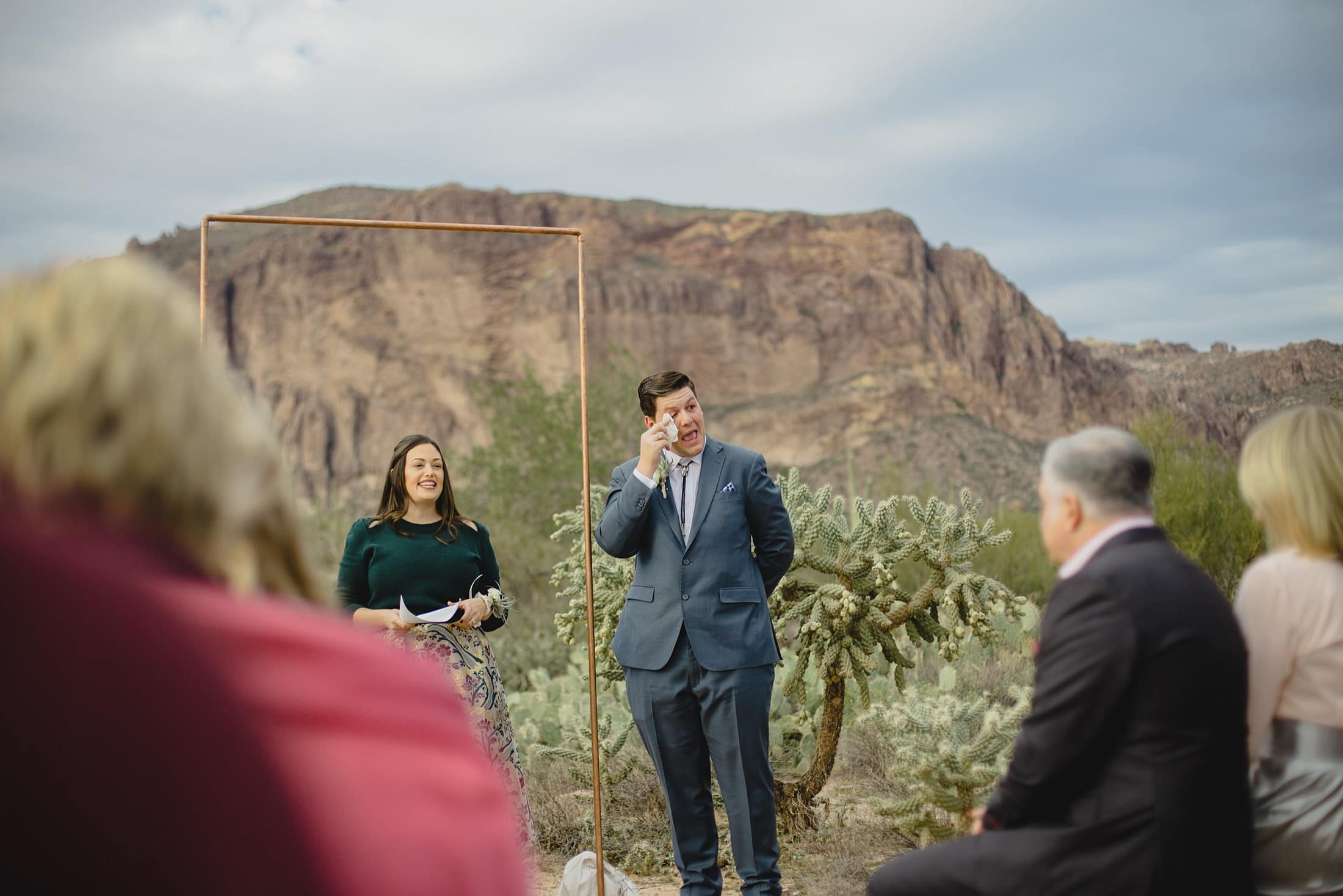 emotional groom seeing bride for first time down aisle in Arizona desert wedding