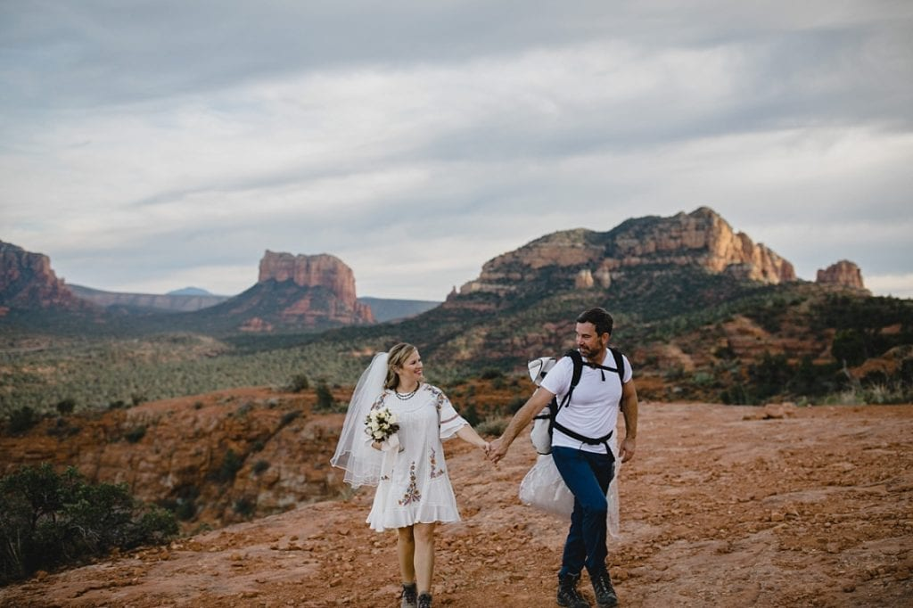 Bride and groom in hiking boots hike cathedral rock to spot for elopement in Sedona