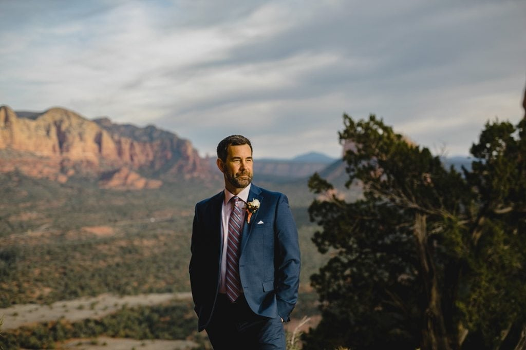 Groom waits for first look of the bride on the wedding day with red rock mountains and trees behind him