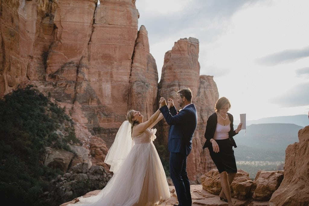 Bride and groom cheers and holds hands when being pronounced married in Sedona