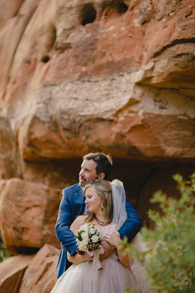Bride and groom hug and look to the left admiring the Sedona mountains
