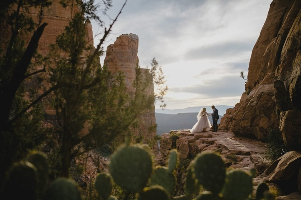 Married couple on edge of rock cliff taking photos in the Sedona desert