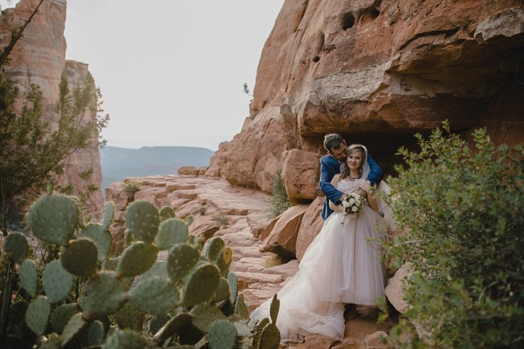 Married couple cuddle for wedding photos in Sedona with cactus and red rocks