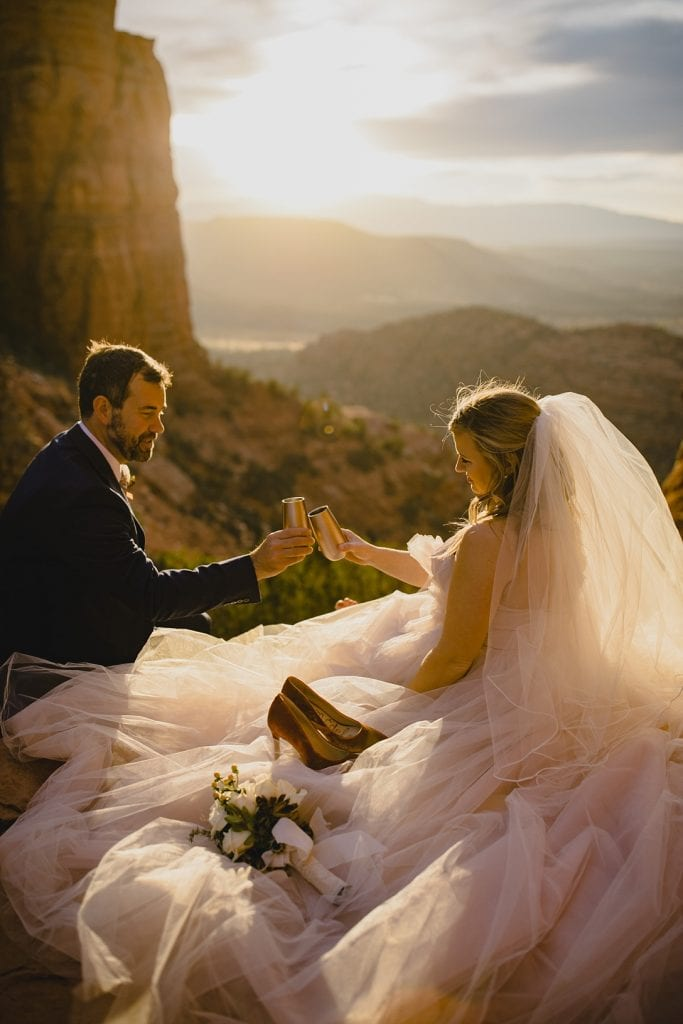 Bride and groom cheers their champagne glasses while watching the Sedona sunset