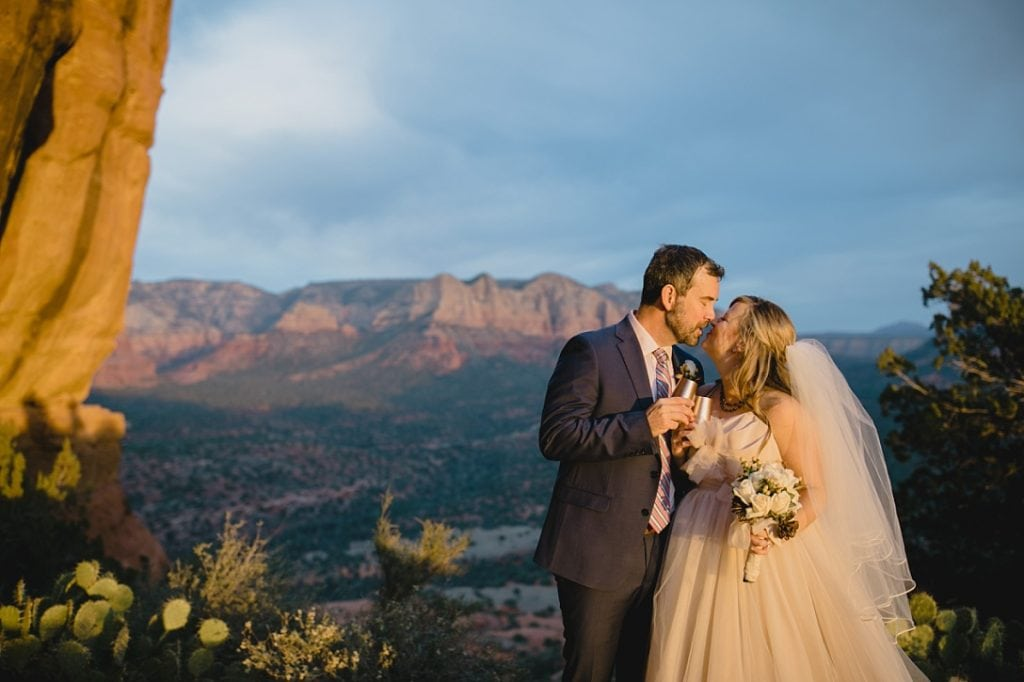 Wedding couple toasting champagne in Sedona at sunset