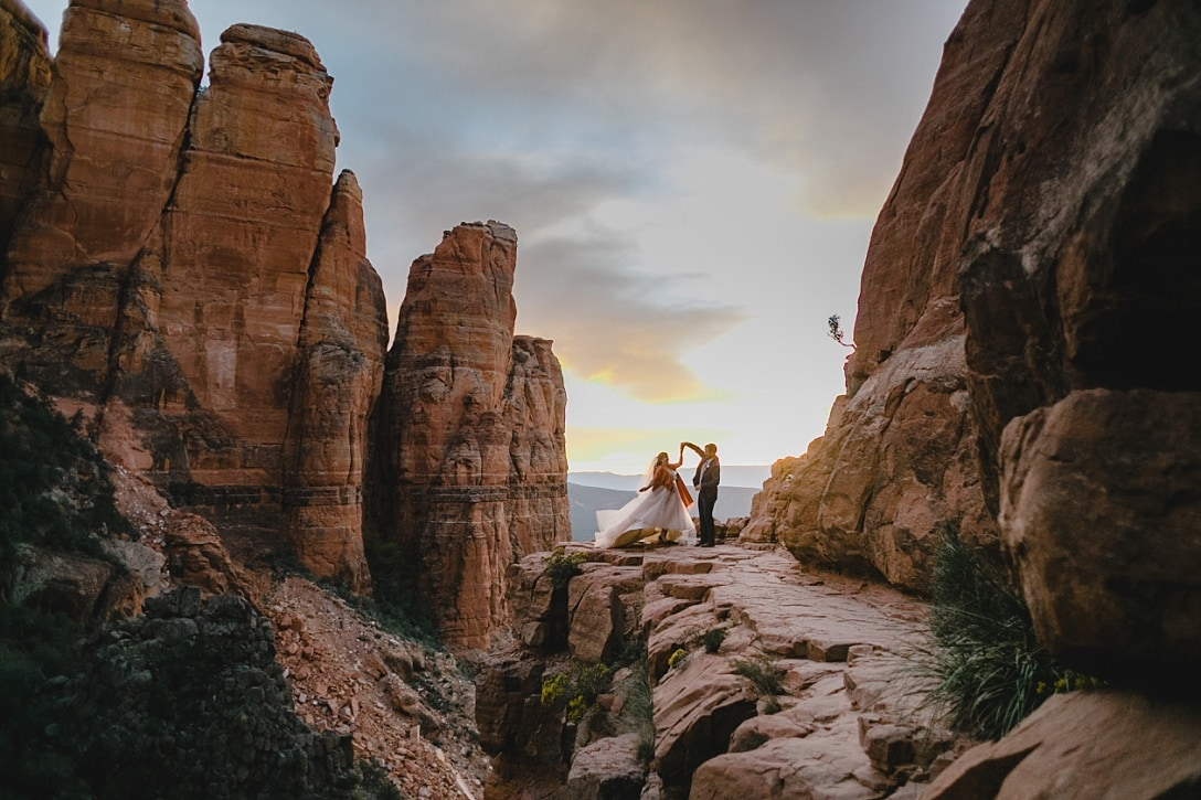 Wedding couple at sunset at Cathedral Rock in Sedona dancing with a blush tulle dress
