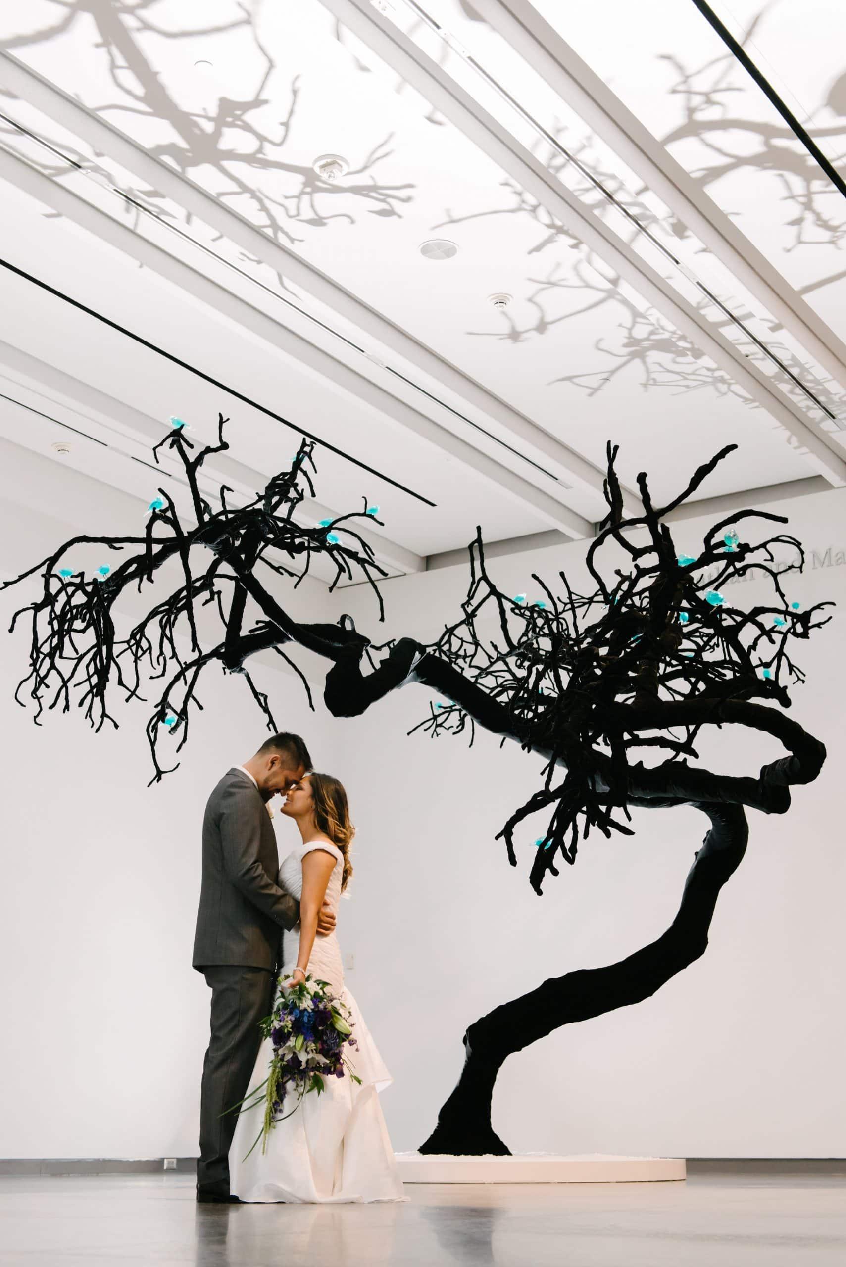 Phoenix Art Musuem wedding couple standing in front of black tree indoors part of art exhibit