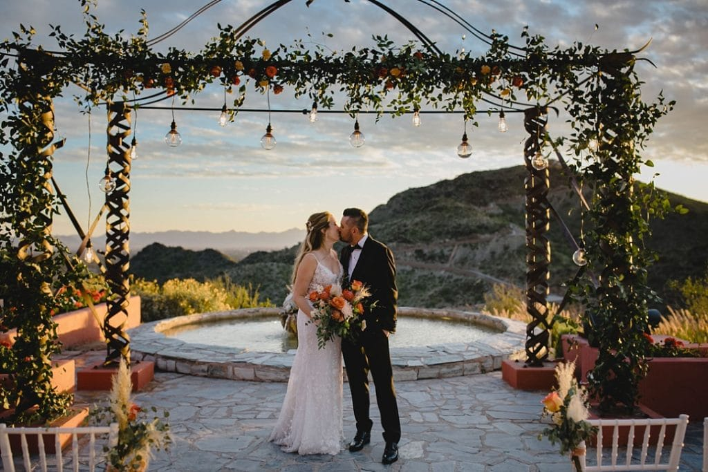 elegant mountaintop Phoenix wedding venue with iron arch and hanging lights and florals