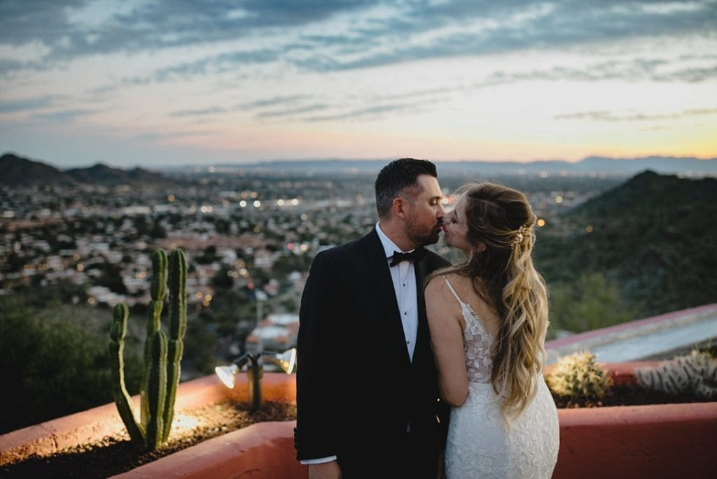 Different Pointe of View Tapatio Cliffs wedding with bride and groom kissing at sunset on mountain with Phoenix city lights below